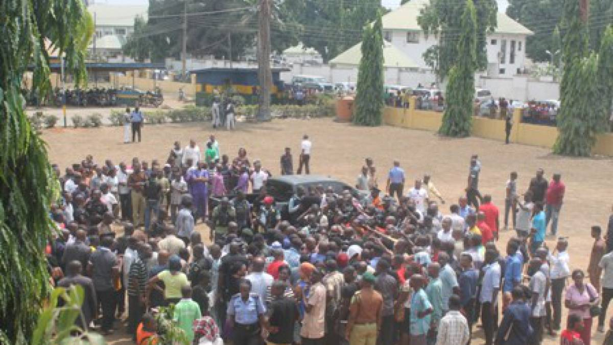 Locals gather around police as they parade arrested kidnappers